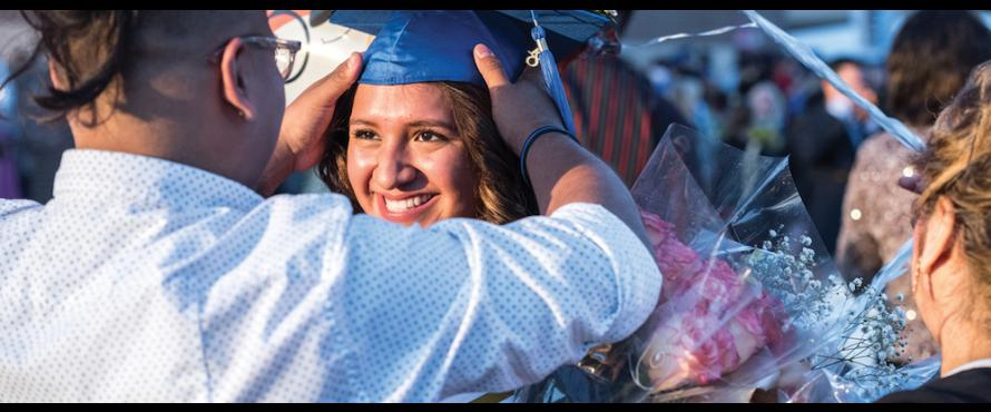 A person adjusts the blue mortarboard on the head of a smiling female graduate