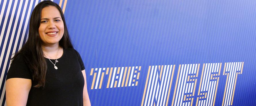 "Photo of Isabel Vargas wearing a black shirt in front of a white, blue, and yellow wall that reads ""The Nest."""