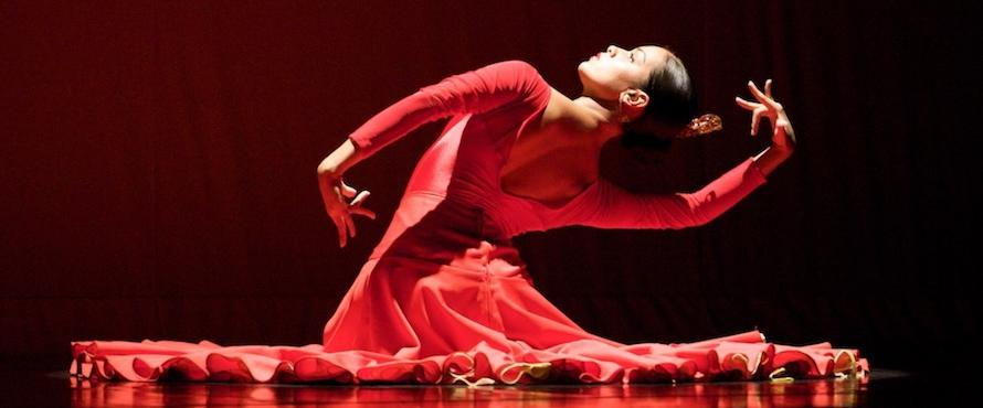 A female dancer wearing a red dress poses against a black background