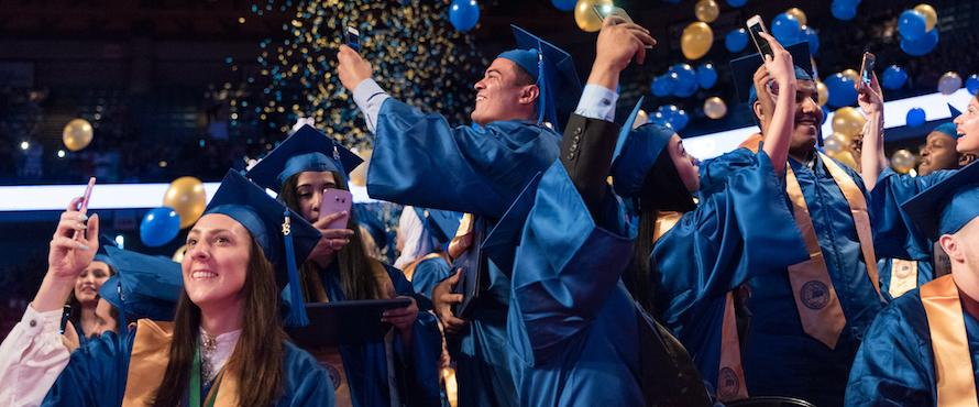 Graduates wearing blue caps and gowns celebrate at Commencement