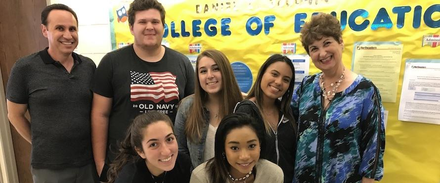 Photo of Daniel L. Goodwin College of Education Dean Sandra Beyda-Lorie (right) and Instructor Bill Kondellas (left) pose with Ridgewood students Yilyanny Barreto-Rodriguez, David Berry, Julie Clark, Ivy Huynh and Abriela Karemanaj.
