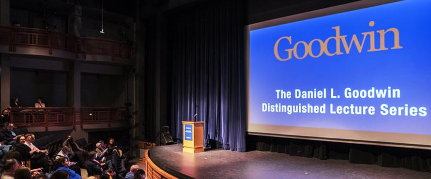 "Photo of the Northeastern Main Campus Auditorium stage with an empty podium and screen that reads ""The Daniel L. Goodwin Distinguished Lecture Series"" in white text on a blue background"