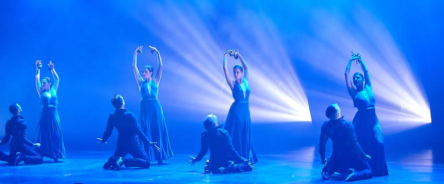 Eight dancers strike poses on stage under blue lighting