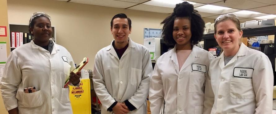 Four smiling students wearing white lab coats stand side by side in a laboratory