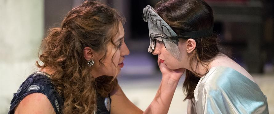 "Two women look into each other's eyes in ""Antigone"""