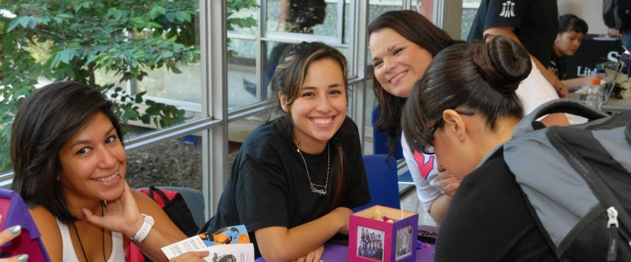 Three women smiling at a Greek Life tabling event in Village Square