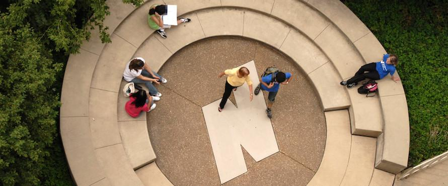 Seen from directly above, people sit and walk near a resting space that has the Flying N logo in the center