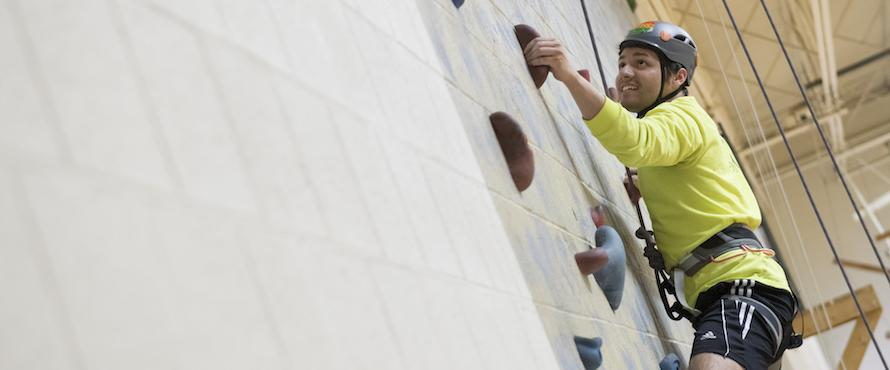 Student Climbs rock wall at the PE complex