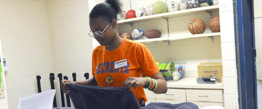 Female student employee folding towels