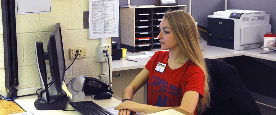female student employee behind computer