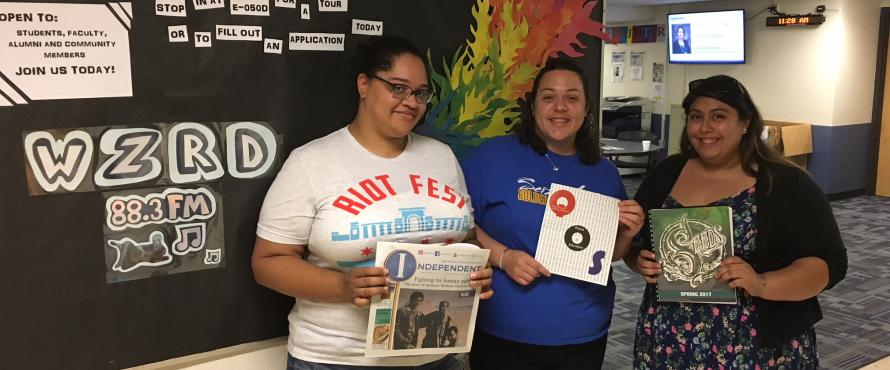 Students from the Independent, Que Ondee Sola and Seeds pose with their publications in front of the WZRD radio bulletin board.