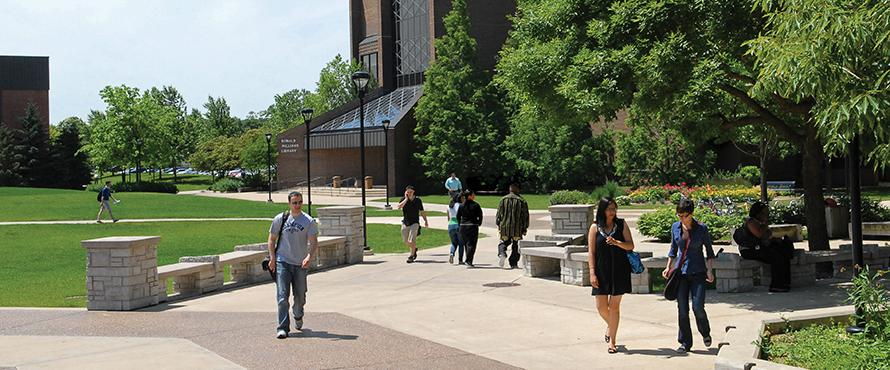 Students walking around campus on a sunny day.