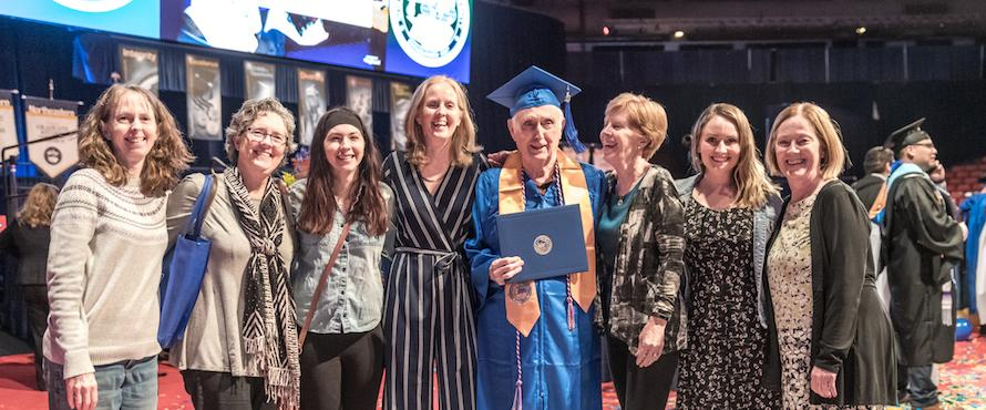 Photo of Bob Dwyer in his blue cap and gown surrounded by his family at Northeastern's May 2019 Commencement.