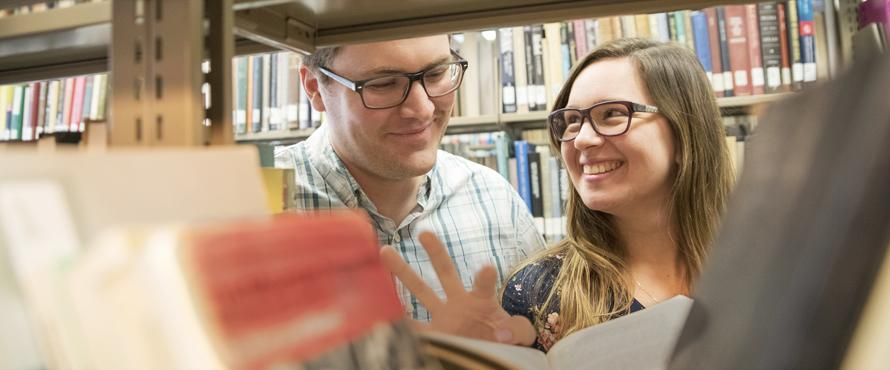 Photo of John and Marianela Crissman looking at a book in the Ronald Williams library.