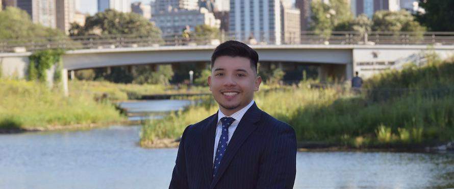 A photo of Julio Arreola with the Chicago River and city skyline behind him