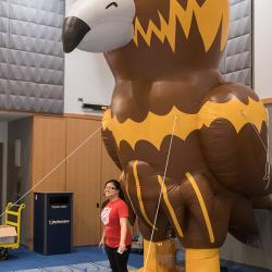 Giant inflatable Goldie mascot towers over a student.