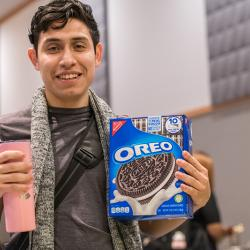 Student poses with a box of Oreo cookies.