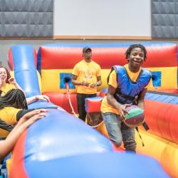 Student in inflatable bungee-basketball court holds ball with big smile preparing for shot as onlookers smile and laugh