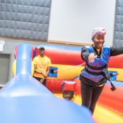 Student in inflatable bungee-basketball court holds ball stretches bungee cord and has arms in air waiting for shot to land