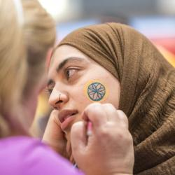 Student turns her head sideways while body artist paints a flower on her cheek in NEIU blue and gold