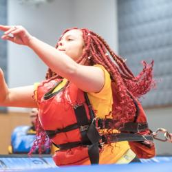 Student with bright red dreadlocks in inflatable bungee-basketball court stretches bungee chord has arms in air waiting for shot to land