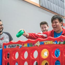 Student playing giant connect 4 holds smiles widely as he places green disk