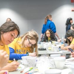 Students, including FYE peer mentors, paint flower pots for Spring Time