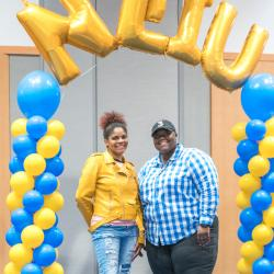 Two students pose below NEIU balloon marquee