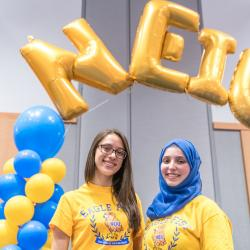 Two female students pose underneath golden Mylar balloons that spell out NEIU