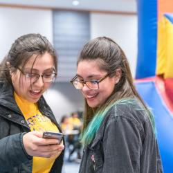 Two students smiling and connecting over a cellphone