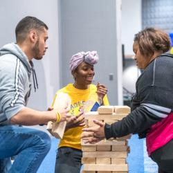 Two students playing giant Jenga watch with tension and joy as a third student removes a block from the tower