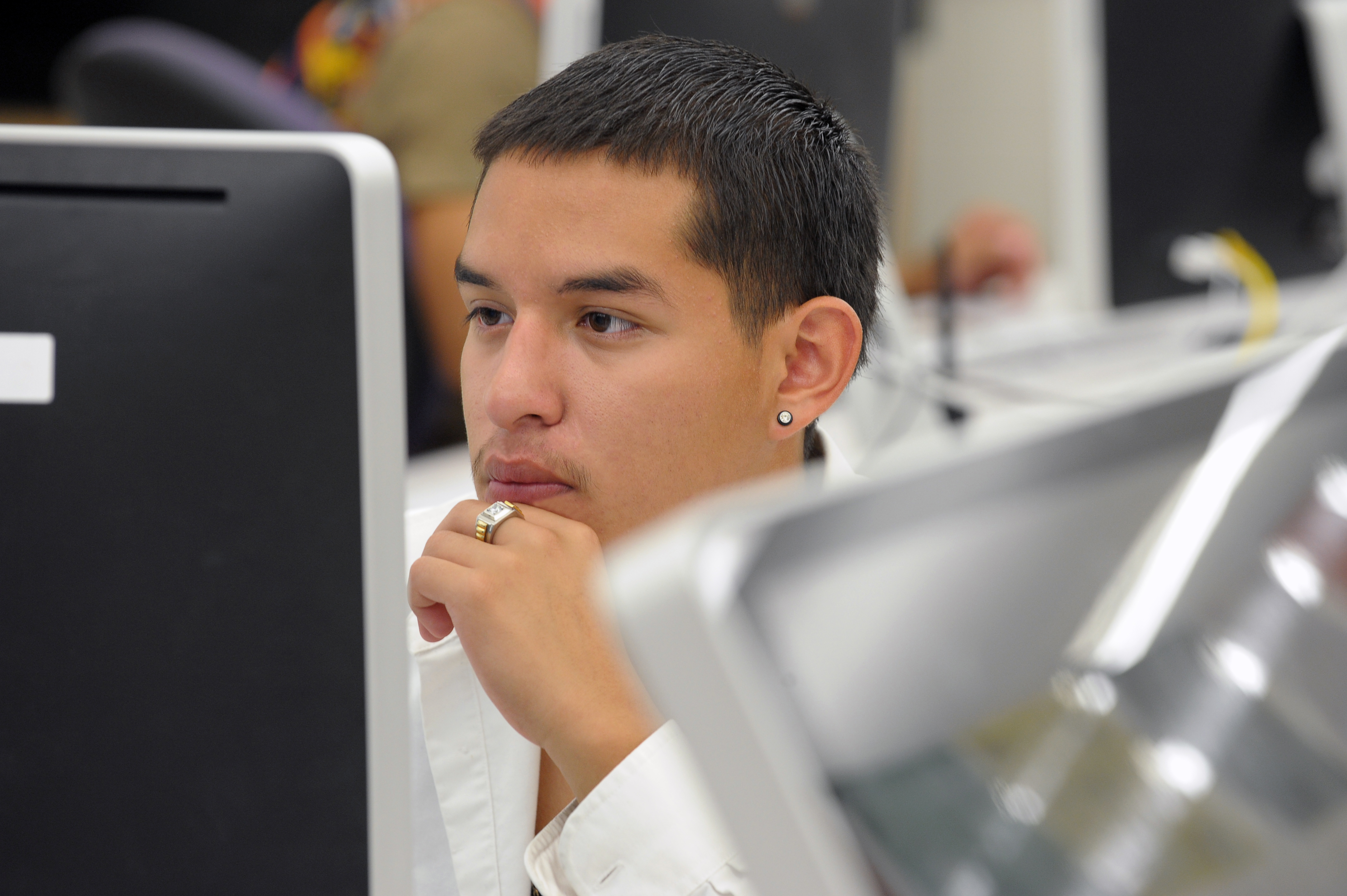 A male student sitting at a computer monitor