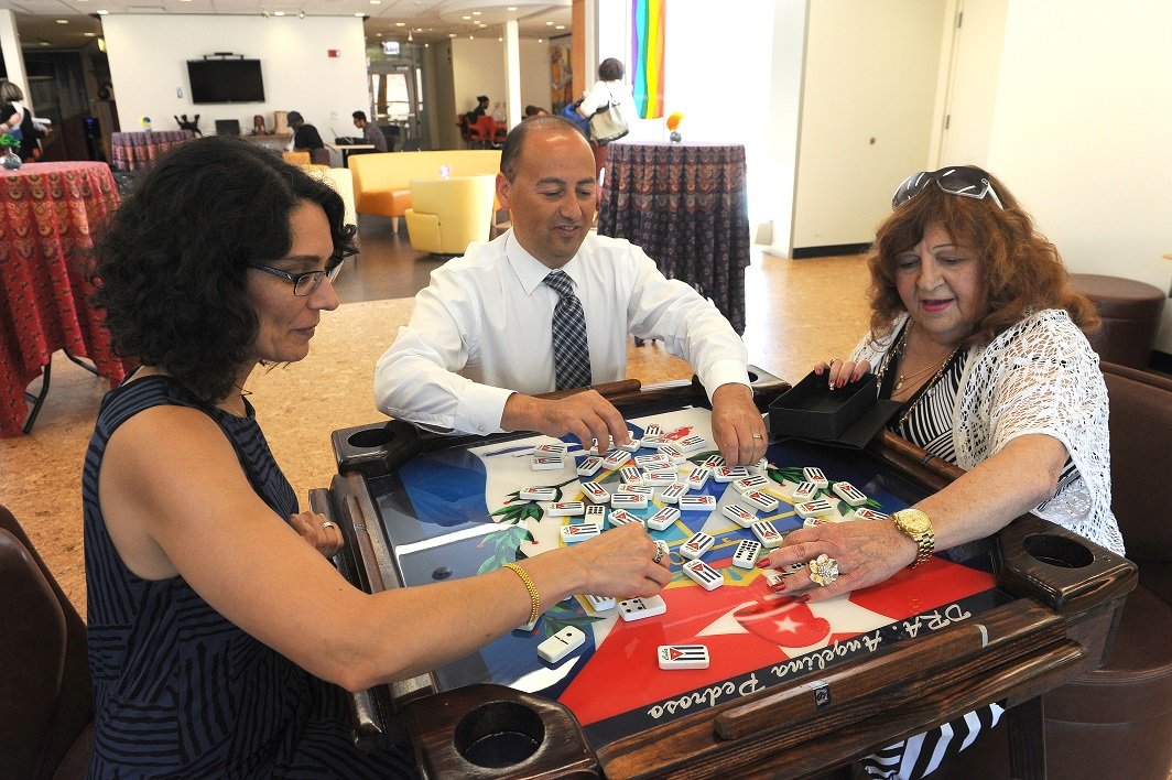 First game on Pedroso Center's new domino table donated in honor of Dr. Pedroso.