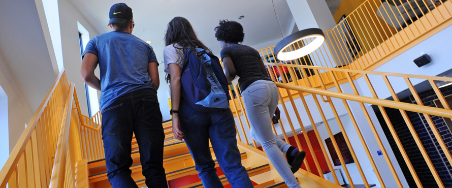 Three students walk up the stairs in the entryway of The Nest residence hall.