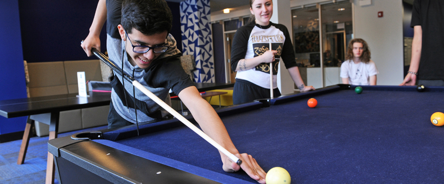 Students congregate around the pool table in The Nest lobby.