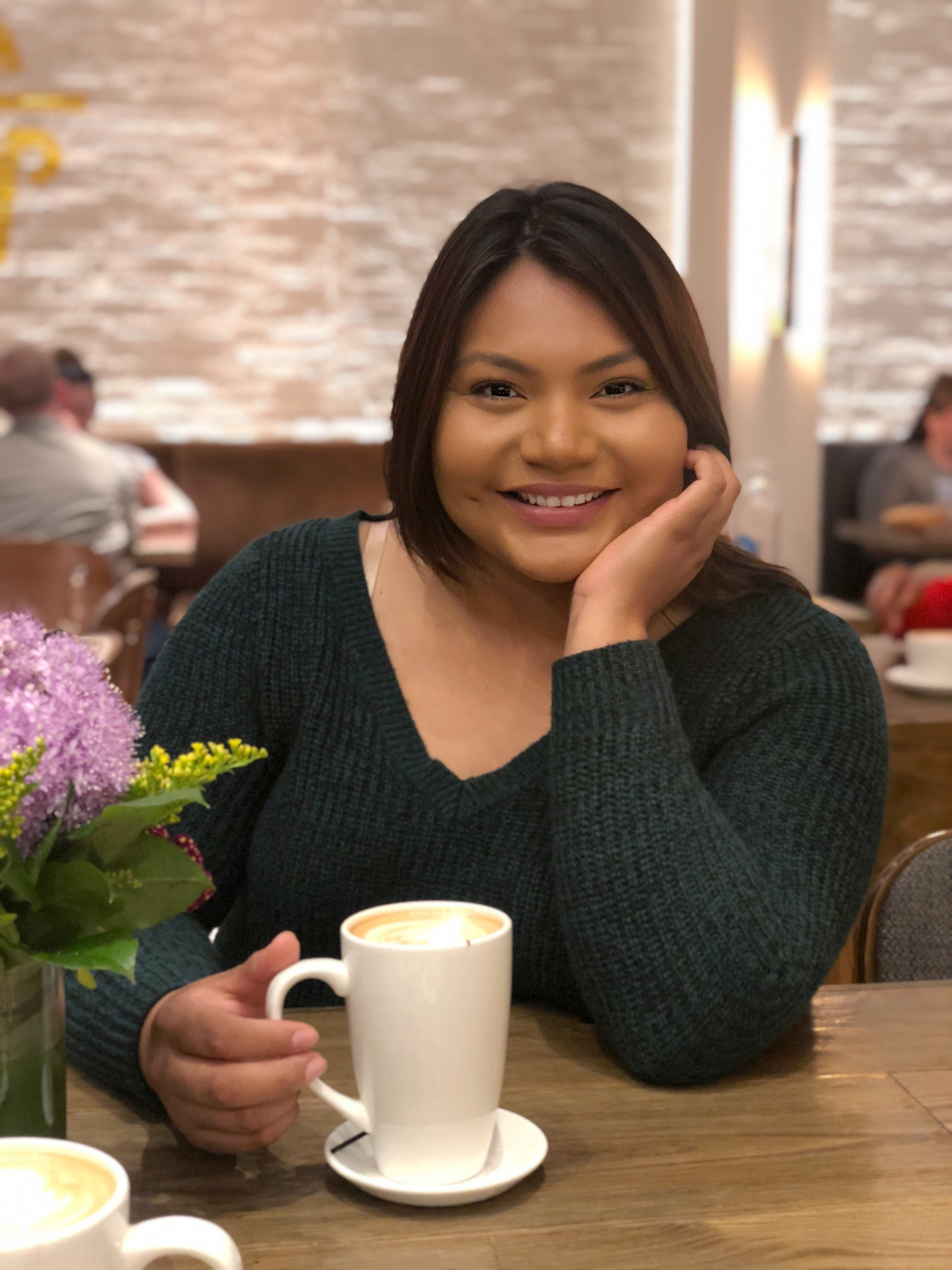 Cecelia Hernandez smiles into the camera while holding a cup of coffee.