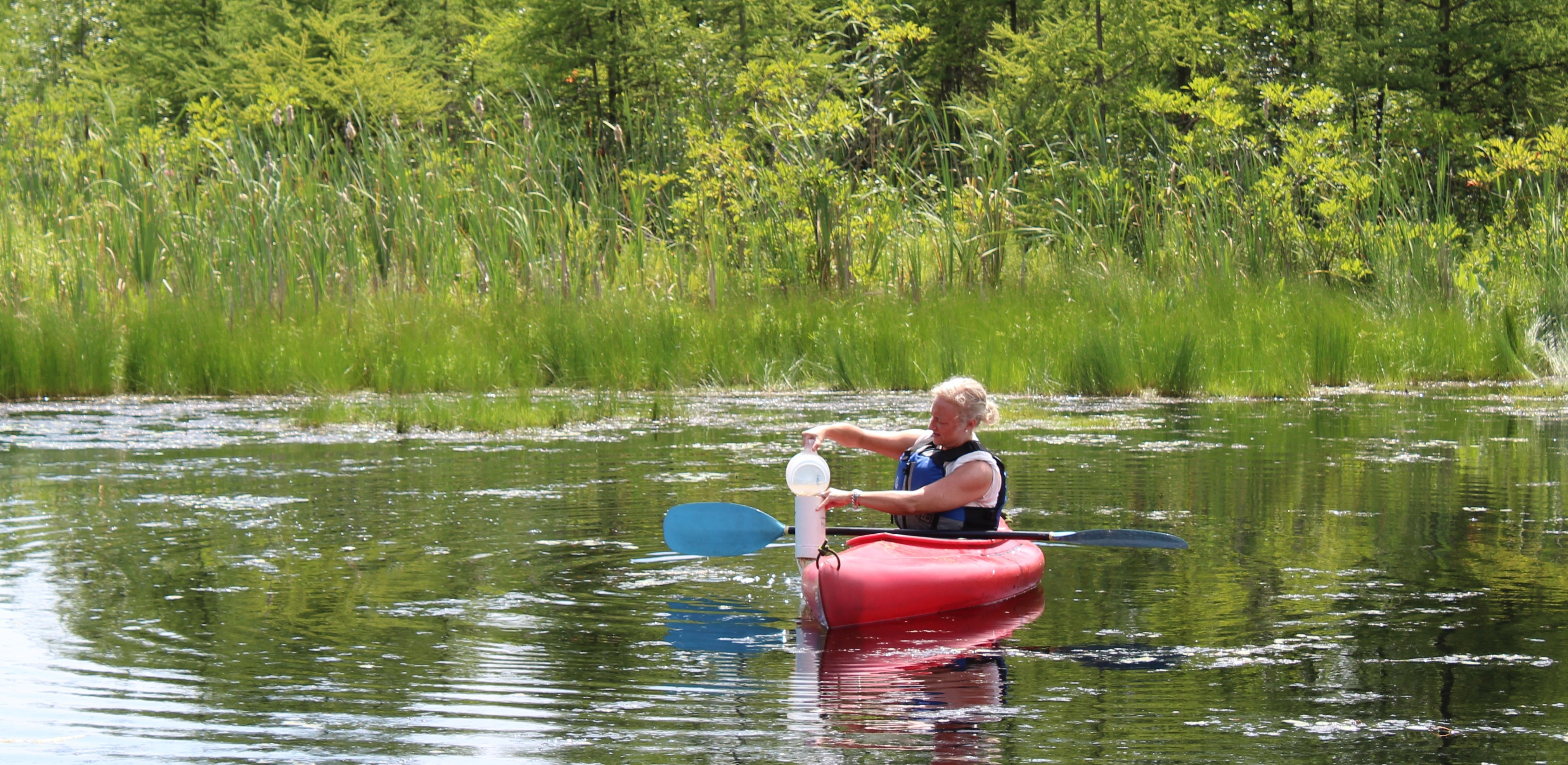 """Pam on a lake in a kayak taking a water sample"""