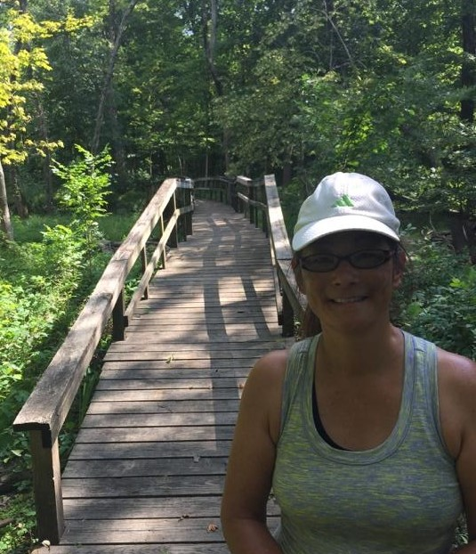 """Maureen in front of a wooden bridge"""