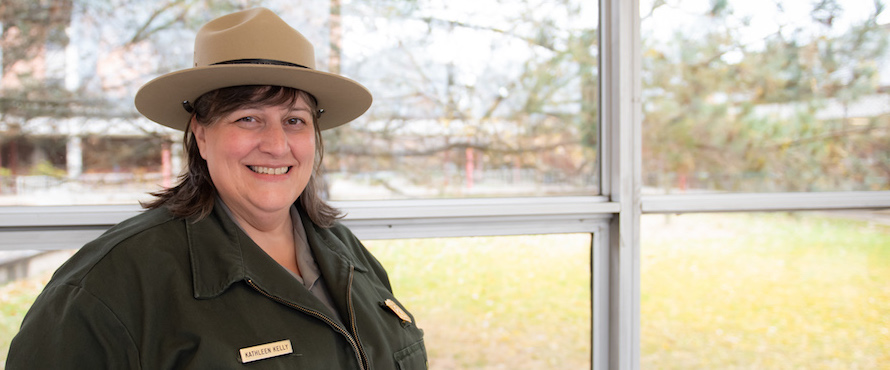 Kathleen Kelly smiles into the camera while wearing her park ranger uniform.
