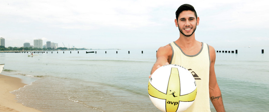 Raffe Paulis holds up an AVP volleyball toward the camera while standing on the beach of Lake Michigan.